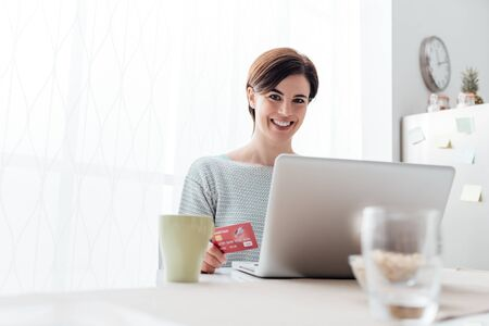Smiling young woman connecting with a laptop in the kitchen at home, she is doing online shopping and buying products using a credit card