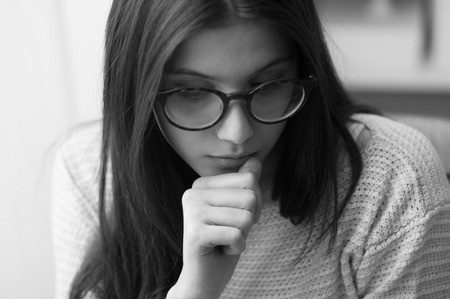 Sad nervous teenage girl with glasses, she is biting nails and looking down