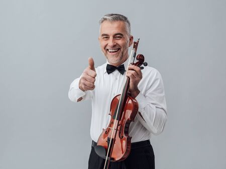 soloist: Cheerful violinist posing with a violin and giving a thumbs up Stock Photo