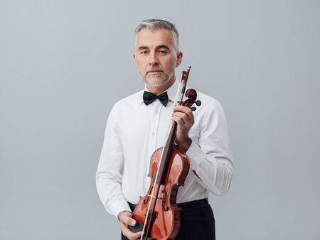 Confident mature musician posing with a violin and looking at camera, classical music and entertainment concept Stock Photo