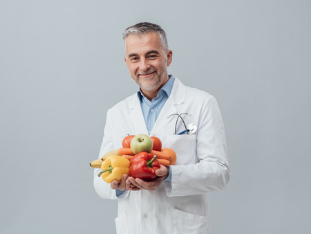 dietetics: Smiling nutritionist holding fresh vegetables and fruit: healthcare and healthy vegetarian diet concept