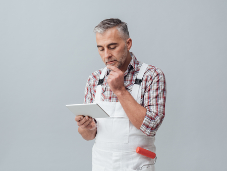 Professional painter connecting with a digital tablet and thinking with hand on chin, he is searching products online