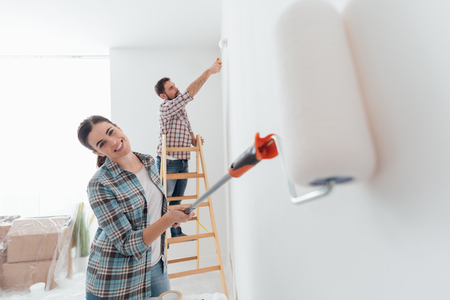 Home makeover and renovation: young happy couple painting their new house interiors using paint rollers Stock Photo
