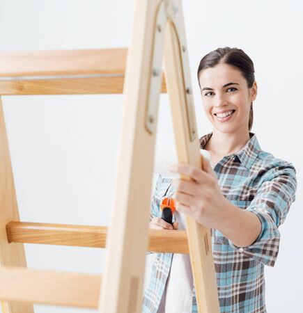 Young smiling woman renovating and decorating her new house, she is holding a paint roller and leaning on a ladder