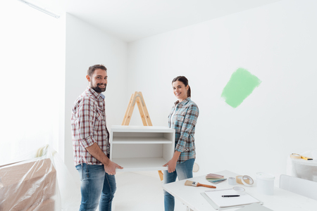 furnishings: Young happy couple renovating their new house and moving furnishings together