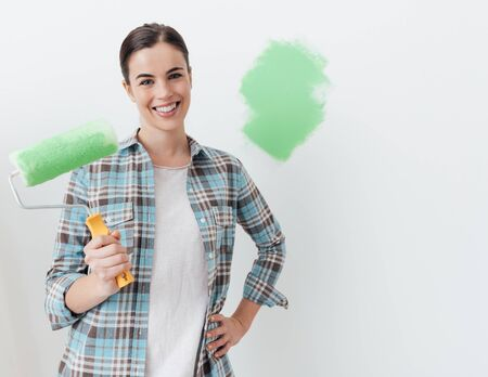 Young smiling woman renovating and decorating her new house, she is using a paint roller and painting walls
