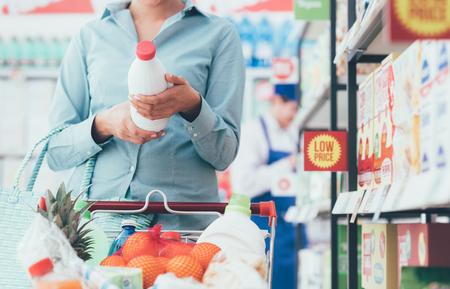 Vrouw die kruidenierswinkel doen die bij de supermarkt winkelen en voedseletiketten, voedings en kwaliteitsconcept lezen Stockfoto