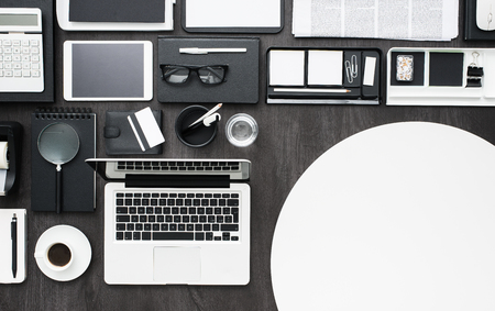 business equipment: Business and management desktop with laptop, tablet, work equipment and a blank circle, flat lay