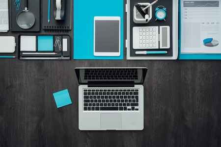 desk tidy: Flat lay corporate business desktop with office accessories and a laptop on a dark background
