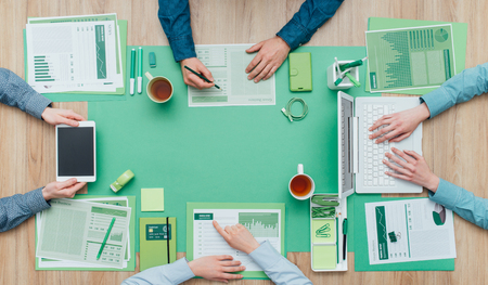 Business people working together on a green desktop, environment, green business and finance concept