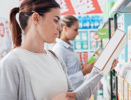 Vrouw winkelen in de supermarkt en lezen voedingsfeiten en ingrediënten op een doos