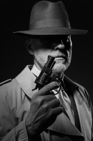 1950s style detective posing in the dark, he is holding a weapon and wearing a fedora hat, noir film character Stock Photo