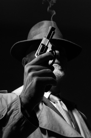 dramatic characters: 1950s style detective posing in the dark, he is holding a weapon and wearing a fedora hat, noir film character Stock Photo
