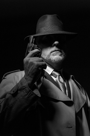 dramatic characters: Detective holding a gun in the dark, he is wearing a fedora hat and a trench coat, 1950s noir movie character