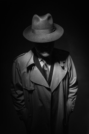 Man posing in the dark with a fedora hat and a trench coat, 1950s noir film style character Stock Photo - 74379368