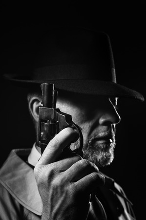 Detective holding a gun in the dark, he is wearing a fedora hat and a trench coat, 1950s noir movie character