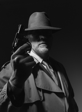dramatic characters: Undercover agent holding a pistol in the dark, 1950s noir film character Stock Photo