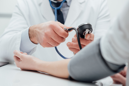 Doctor checking blood pressure of a patient, he is measuring pulses with a sphygmomanometer, hands close up Stock Photo - 74391679
