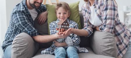 madre trabajando: familia feliz que sostiene una casa modelo y posando juntos: mejoras para el hogar, bienes raíces y concepto de hipoteca