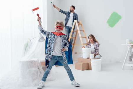 Family renovating their home and painting walls, the boy is wearing a superhero costume and holding a paint roller Stock Photo - 74449725