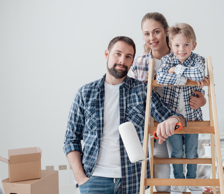 Happy young family doing a home makeover, they are posing together, the man is holding a paint roller and the woman is holding her son on a ladder Stock Photo