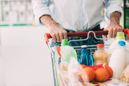 necessities: Man doing grocery shopping at the supermarket, he is pushing a full trolley, hands detail close up Stock Photo