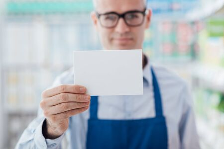 Smiling supermarket worker holding a blank white sign and looking at camera, shelves on the background Stock Photo