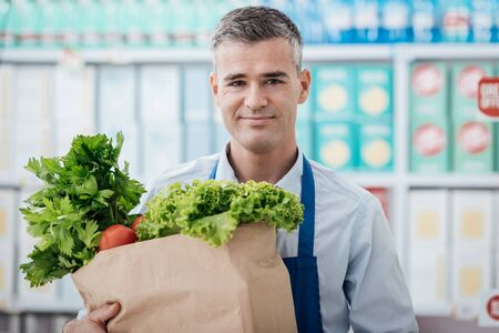 Professional supermarket clerk holding a grocery bag with fresh vegetables, freshness and healthy food concept Stock Photo