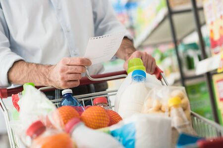 lifestyle shopping: Man at the supermarket shopping with a grocery list and pushing a full cart, lifestyle and retail concept Stock Photo