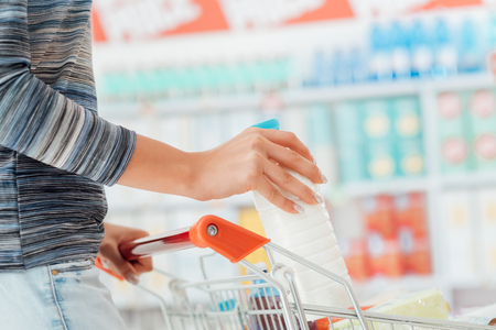 necessities: Woman doing grocery shopping at the supermarket and pushing a full shopping cart, hand detail close up, lifestyle concept Stock Photo