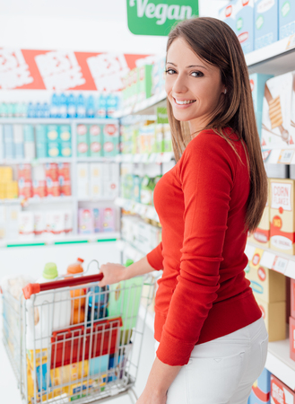 Smiling woman shopping and pushing a full cart along the grocery aisles, back view