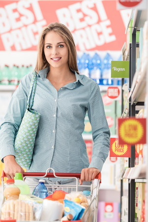 Happy woman shopping at the discount store, she is pushing a full trolley along the supermarket aisles and smiling at camera