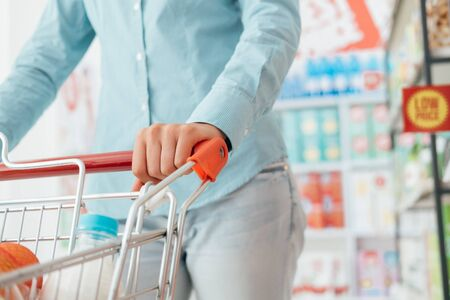 lifestyle shopping: Woman doing grocery shopping at the supermarket, she is pushing a full shopping cart, hand close up, lifestyle and retail concept