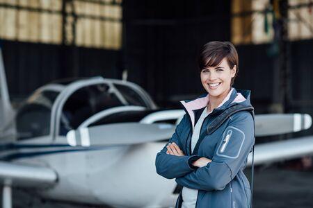 Lächelnde junge Frau, die mit ihrem Flugzeug im Hangar vor Abflug-, Luftfahrt- und Leichtflugzeugkonzept aufwirft