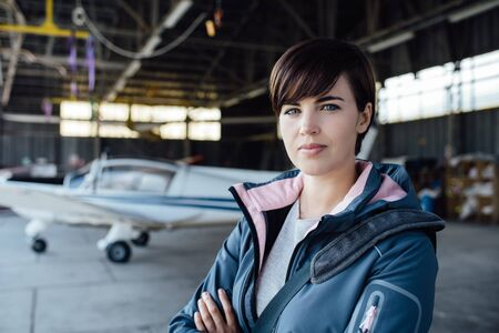 airplane ultralight: Confident young female pilot posing in the hangar with arms crossed, airplane on the background