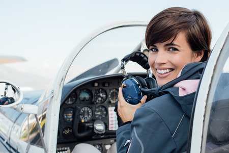 Smiling female pilot in the light aircraft cockpit, she is holding aviator headset and looking at camera