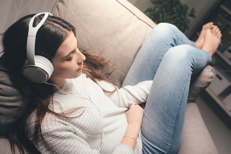 Girl sleeping on the armchair at home late at night, she is wearing headphones and listening to music Stock Photo