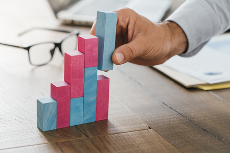 Businessman working at office desk, he is building a growing financial graph using wooden toy blocks: successful business concept
