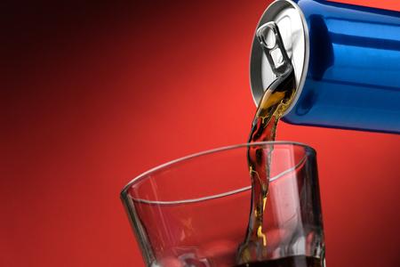 Een verfrissende, suikerzoete frisdrank uit een blik in een glas gieten