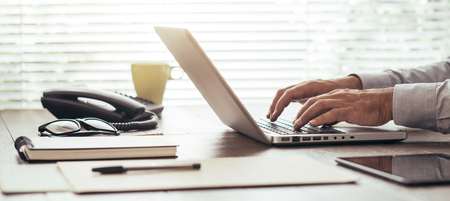 Corporate businessman sitting at office desk and working with a laptop next to a window