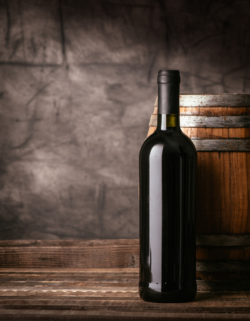 Red wine bottle and wooden barrel in the cellar, traditional wine making and tasting concept