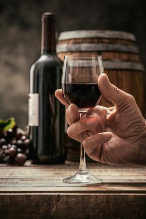 年配の男性が彼のセラー、ワインの瓶、ブドウ、背景にバレルで高価な赤ワインのグラスを飲むワインの伝統と文化の概念 写真素材