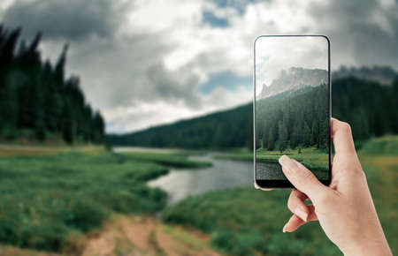 photo edges: Tourist taking a picture of Dolomites and nature scenics using a smartphone, point of view shot
