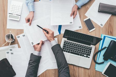 Bedrijfsmensen die bij bureau werken, controleren zij belastingsvormen en berekenend kosten, financiën en beheersconcept Stockfoto