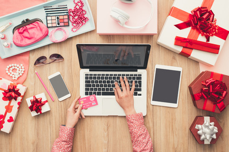 electronic commerce: Woman purchasing beauty and fashion products online using a laptop and a credit card, e-commerce and electronic payments concept