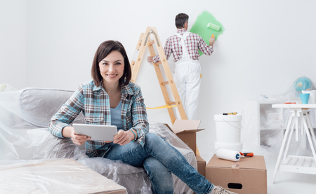 Happy woman relaxing and connecting with her tablet while a painter is painting the room, home renovation concept