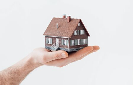 insurer: Man holding a model house: real estate, insurance and home loan concept