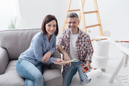 Home renovation and decoration: couple choosing colors for their house walls, ladder and paint buckets on the background
