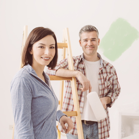 Smiling couple painting their house, they are posing and leaning on a ladder, home renovation concept