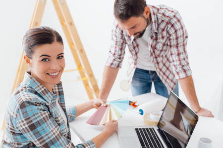 Young smiling couple renovating their home, they are choosing paint color swatches together